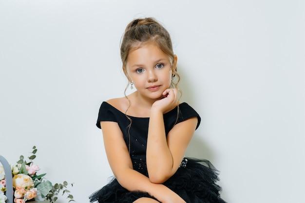 검은 드레스에 귀여운 소녀가 앉아 꽃의 꽃다발과 함께 웃고 있습니다.
