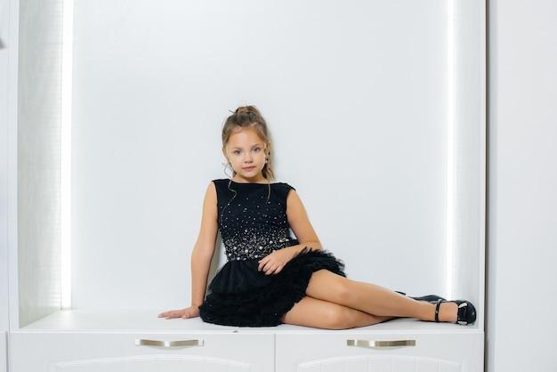 검은 드레스에 귀여운 소녀가 앉아서 흰색 배경에 포즈.