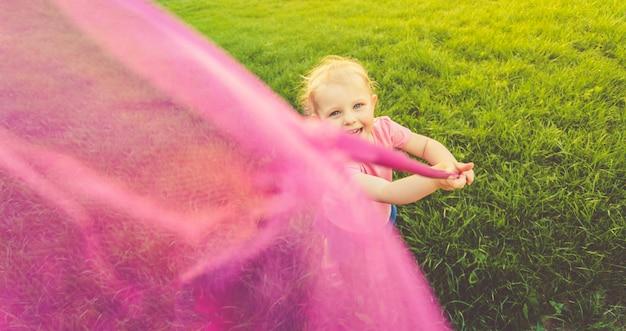 분홍색 티셔츠와 데님 치마에 귀여운 소녀가 들판을 돌아 다니며 나비를 잡습니다. 라이프 스타일.