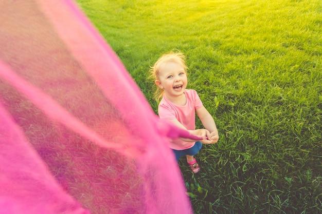 분홍색 티셔츠와 데님 치마에 귀여운 소녀가 들판을 돌아 다니며 나비를 잡습니다.