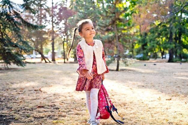 빨간 드레스를 입은 귀여운 소녀 여학생이 배낭을 메고 가을 공원을 산책한다