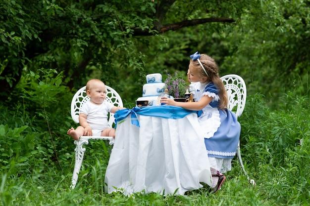 Маленькая милая девочка в костюме «алиса из страны чудес» и ее годовалый брат устраивают чаепитие за волшебным столом. снято на природе.
