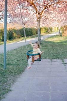 귀여운 소녀가 피는 정원에서 그네를 타고 있습니다. 봄.