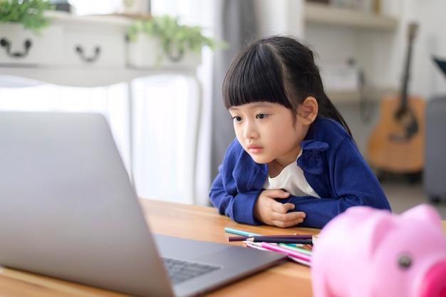 かわいい女の子が自宅でインターネットを介してオンラインで勉強するためにラップトップを使用しています。隔離期間中のeラーニングの概念。