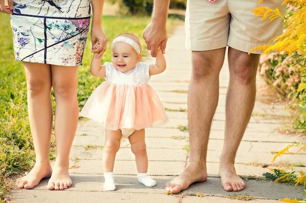 かわいい女の子が両親と手をつないで歩くことを学ぶ Premium写真