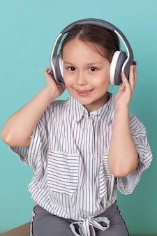 작은 귀여운 소녀는 파란색 배경에 큰 헤드폰으로 음악을 듣습니다.