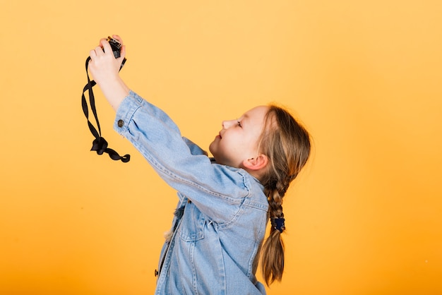 노란색 벽에 사진을 만드는 작은 귀여운 소녀.