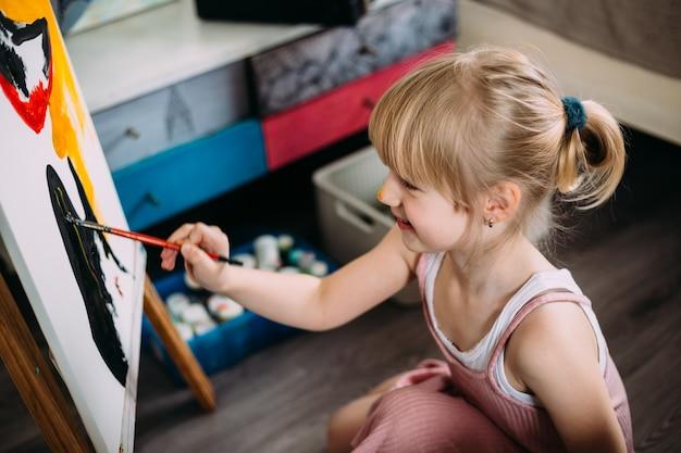 Маленькая милая девочка пишет большую картину акрилом дома на мольберте