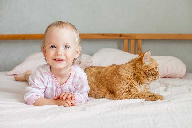 작은 귀여운 소녀는 뚱뚱한 생강 고양이 스트로크와 함께 침대에 앉아 그와 함께 노는 프리미엄 사진
