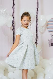 Маленькая милая девочка улыбается и позирует на фоне качелей с воздушными шарами