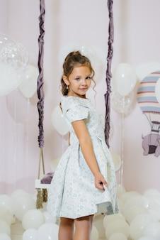 귀여운 소녀 미소와 풍선 스윙의 배경에 포즈.