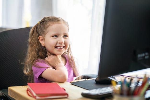 コンピューターをリモートeラーニングに使用しているかわいい女の子。