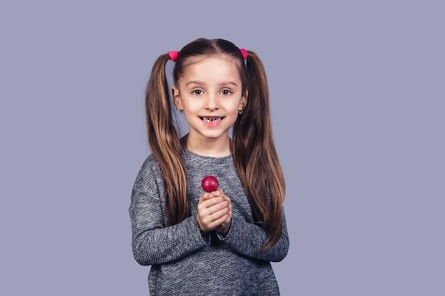 彼女の手に赤いロリポップを持つ小さなかわいい女の子は、彼女の甘やかされて育った歯を示しています。キャンディーの乱用による虫歯の概念。灰色の背景に分離