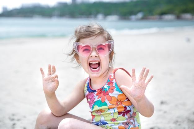 안경을 쓴 귀여운 소녀가 바다 해변의 모래에서 놀고 있습니다.