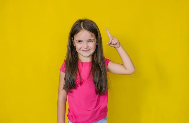 Маленькая милая счастливая девушка смотрит и показывает жест, указывающий на идею.