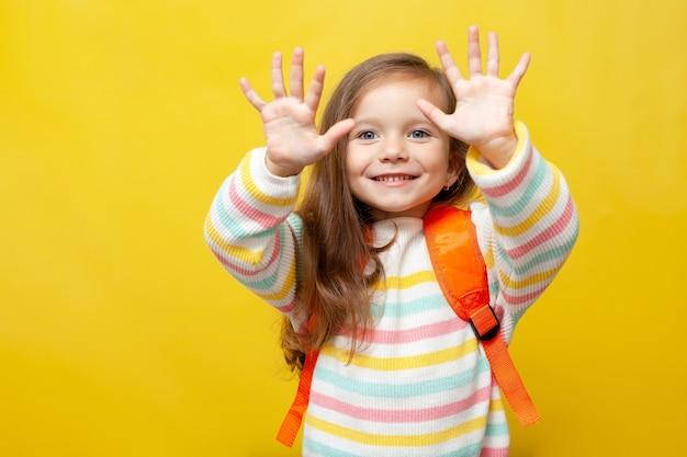 배낭을 메고 있는 귀여운 여학생이 손을 보여줍니다. 노란색 배경