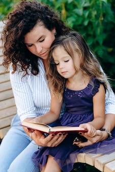 작은 딸과 그녀의 어머니는 재미있는 책을 읽고 공원에서 벤치에 앉아있다