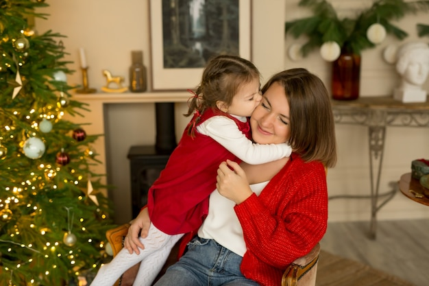 小さな娘がクリスマスイブに母親にキスして抱きしめます