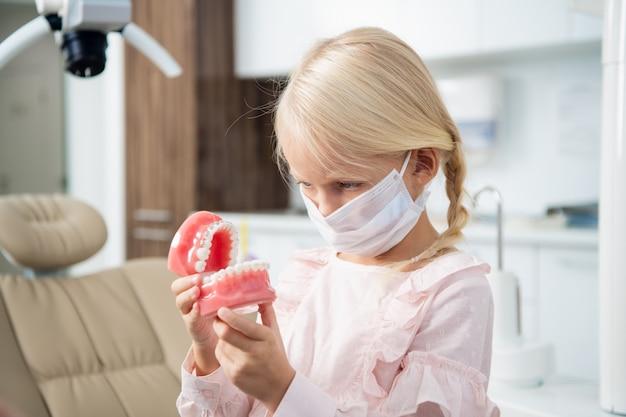 Маленький стоматолог в медицинской маске осматривает искусственные зубы