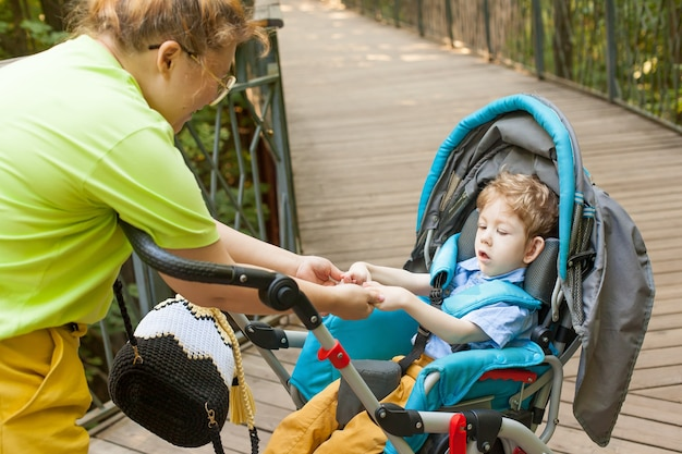 여름날 도시 공원에서 어머니와 함께 휠체어를 탄 장애아. 소아마비. 무능. 포괄성. 이동 제한.