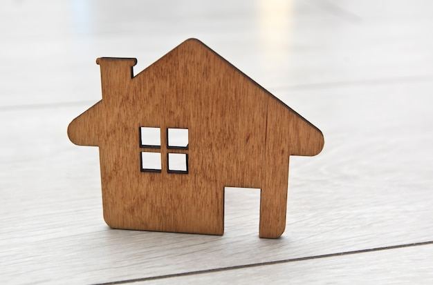 На паркетном полу лежит маленький плоский деревянный дом