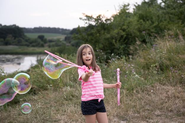 Маленькая забавная девочка дует мыльные пузыри летом в поле, летние занятия на свежем воздухе.