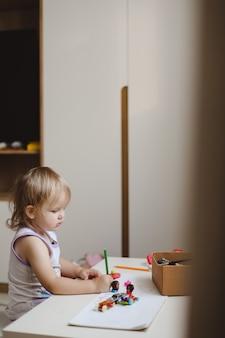 Маленькая забавная девочка рисует карандашами в детской дома