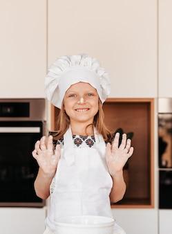 Маленькая забавная девочка в белой шляпе шеф-повара играет с мукой на кухне. детские повара