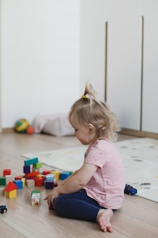 작은 재미있는 소녀는 보육원에서 바닥에 큐브와 장난감을 가지고 노는