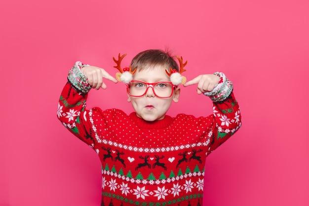 분홍색 배경에 사슴 뿔이 달린 크리스마스 빨간 스웨터와 안경을 쓴 재미있는 아이