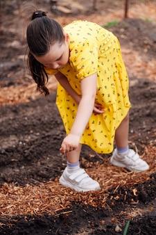 작은 정원사는 정원에서 뒤뜰에 여자 정원 야채를 심는 부모를 돕습니다...