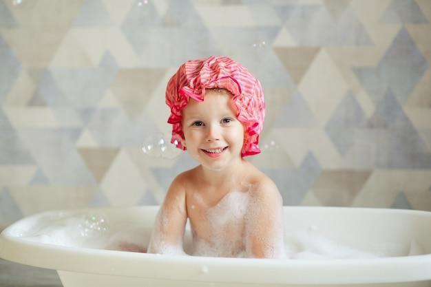 Маленькая девочка 3-4 лет купается в красивой ванной на светлой стене. детская гигиена.