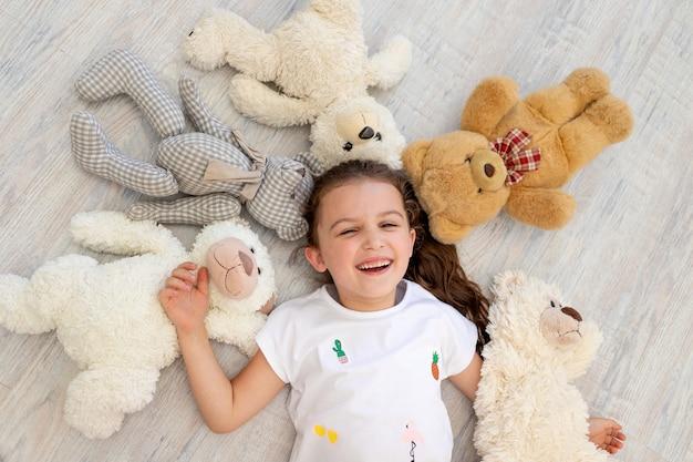 Маленькая девочка 5-6 лет лежит среди мишек тедди