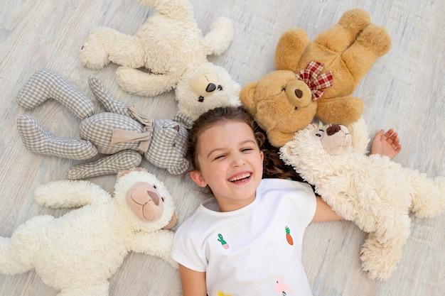 Маленькая девочка 5-6 лет лежит среди медведей тедди