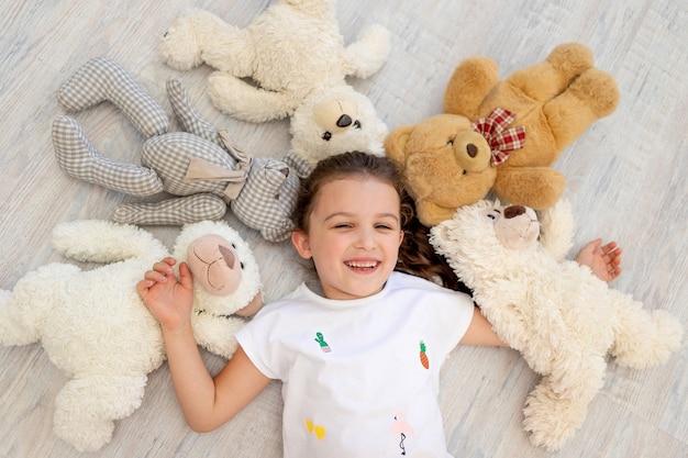 5〜6歳の小さな女の子がテディベアの中にいます
