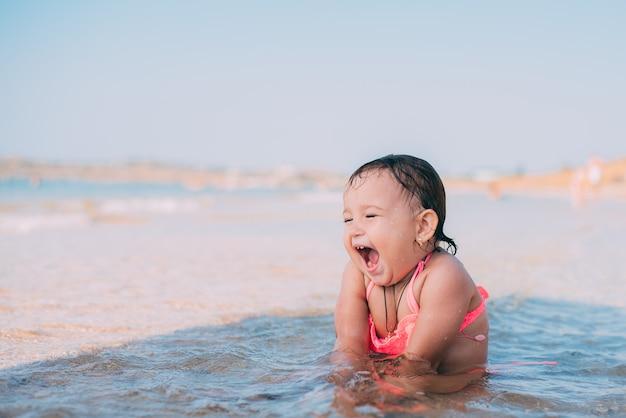 小さな女の子、海に座っているピンクの水着の子供はとても幸せで陽気なです