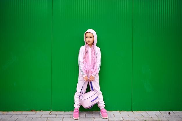 ピンクのジャンプスーツと頭にアフロピグテールをした女子高生が、バックパックを両足の間に挟んでいる。