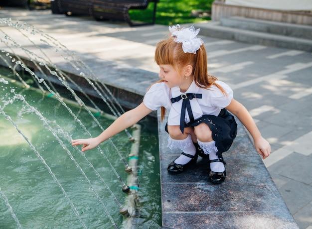 초등학생인 어린 소녀가 분수 근처에서 신나게 놀고 있습니다. 아이는 더운 날 몸을 상쾌하게 할 것입니다. 방과 후 휴식.