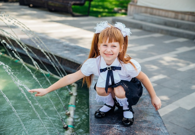 초등학생인 어린 소녀가 분수 근처에서 신나게 놀고 있습니다. 아이는 더운 날 몸을 상쾌하게 할 것입니다.
