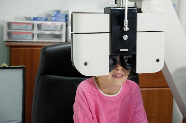 Маленькая девочка проверяет глаза в клинике.