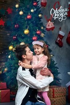 少女と少年が大晦日とクリスマスのクリスマスツリーの近くを抱き締めます。背景のロシア文字の言葉:明けましておめでとう。