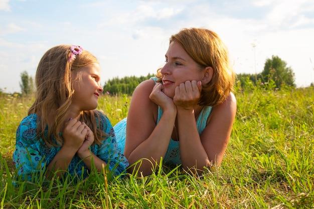 小さな女の子と女性-母親が畑の緑の芝生に横たわり、晴れた夏の天気、子供の笑顔と喜び、娘が子供たちの秘密を語る