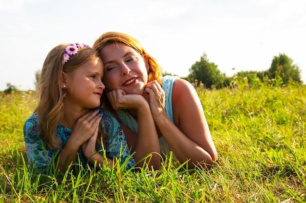 Маленькая девочка и женщина-мама лежат на зеленой траве в поле, солнечная летняя погода, детская улыбка и радость, дочь рассказывает свои детские секреты