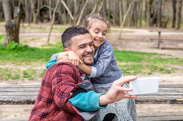 Маленькая девочка и папа фотографируются в парке ранней весной.