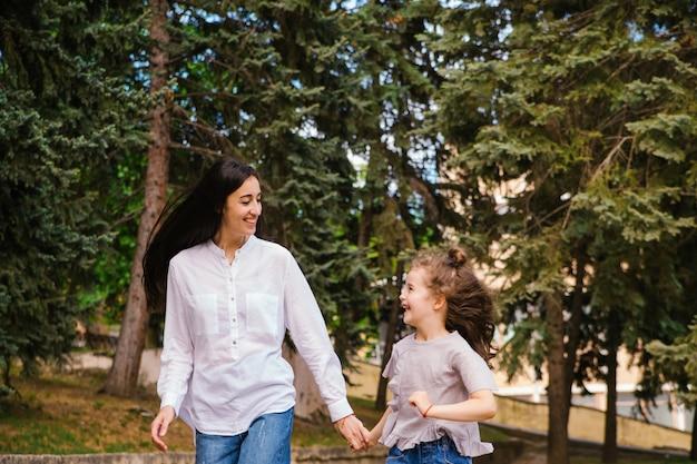 어린 소녀와 그녀의 어머니는 올해의 봄 시간 공원에서 보도를 따라 실행합니다.