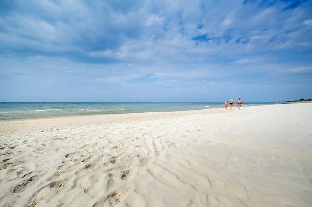 어린 소녀와 그녀의 부모는 리투아니아의 발트해에서 수영복을 입고 해변을 걷고 있습니다.