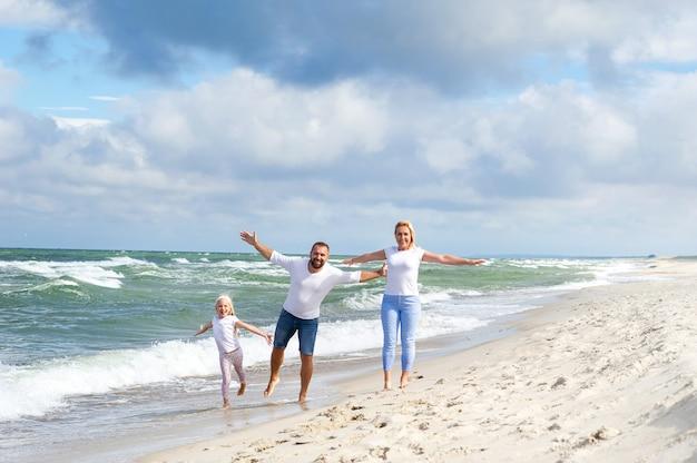 小さな女の子と彼女の両親は、リトアニアのバルト海のビーチを歩きます。