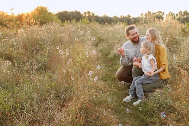 楽しむために自然の中でシャボン玉を持つ少女と彼女の両親