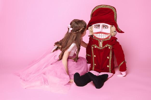 Маленькая девочка как балерина в розовом длинном платье с щелкунчиком в розовой студии