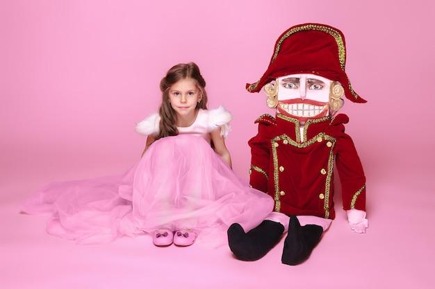 분홍색 스튜디오에서 호두까기 인형이 있는 분홍색 긴 드레스를 입은 미인 발레리나 같은 어린 소녀